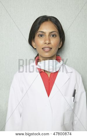 Indian female dentist in lab coat and surgical mask