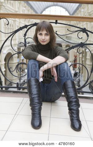 Young Attractive Woman Sitting At Railing In State Department Store. Moscow