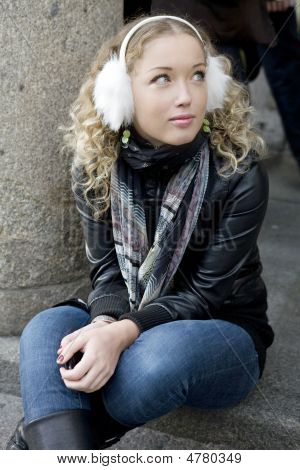 Attractive Girl Sitting On On Pavement In Street In London.