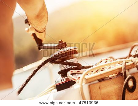 Closeup on man holding crank on the yacht, body part, bright yellow sunset, sailboat detail, active lifestyle, yachting sport, summer relaxation concept