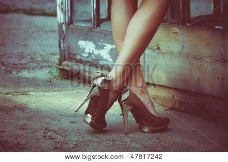 pernas de mulher em sapatos de salto alto contra porta antiga com vidro exterior tiro cores retrô