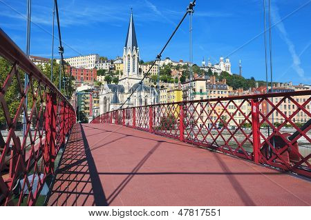 Red Footbridge On Saone River And Church