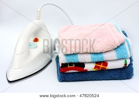 Pile of colorful clothes and electric iron on white background