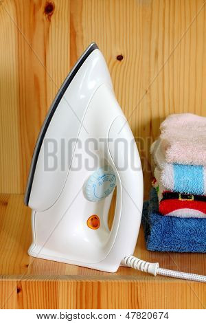 Pile of colorful clothes and electric iron on wood background