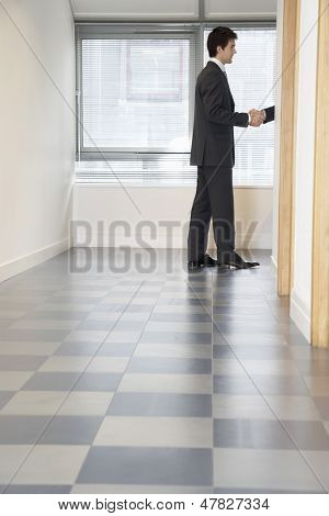 Side view of a businessman shaking hands through doorway with unseen person