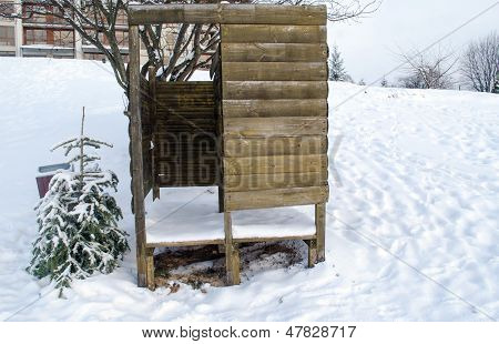 Beach Changing Booth Full Of Snow And Small Tree