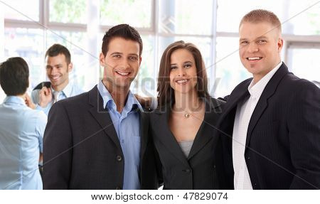 Portrait of successful young business team standing at bright office, smiling happy, looking at camera.