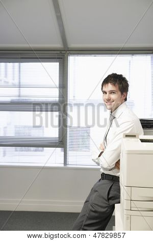 Portrait of a smiling businessman leaning against photocopier in office