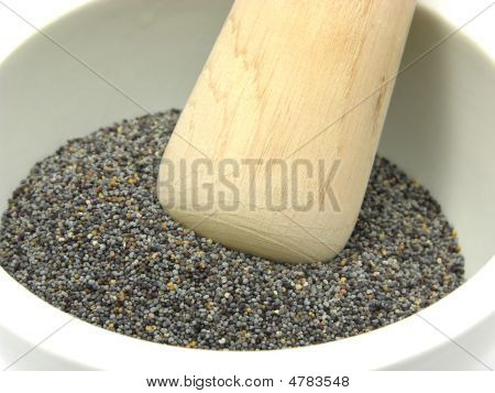 Pestling Poppy Seeds  In A Bowl Of Chinaware