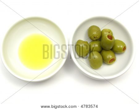 Two Bowls Of Chinaware With Olive Oil And Olives On White Background