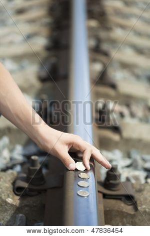 Hand near euro coins on the rails