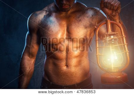 Muscular Man Holding Oil Lamp
