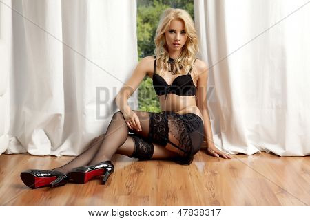 Young adult slim sexy and attractive blonde sensuality woman in black lingerie against the window in apartment
