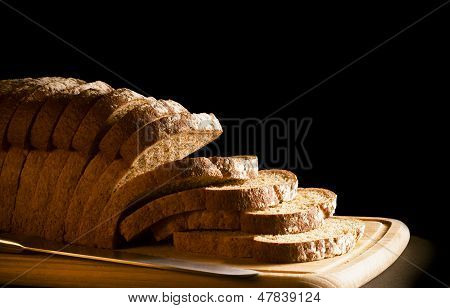 Sliced granary wholemeal loaf of bread on wooden board