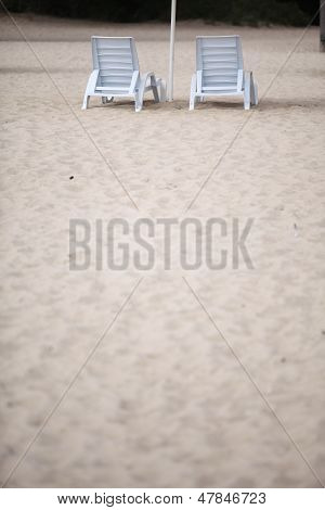 White Pool Chairs On Sand Beach