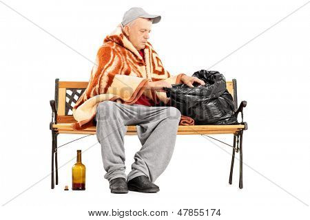 Homeless mature man sitting on a bench and looking for something in his bag, isolated on white background