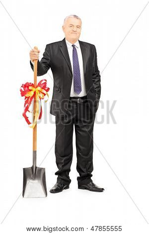 Full length portrait of an investor holding a shovel with ribbon on it and looking at camera isolated on white background