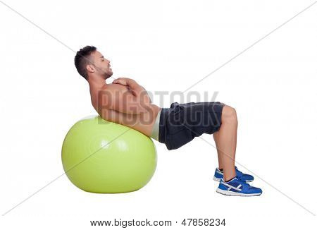 Strong man practicing abdominal on a big ball isolated on a white background