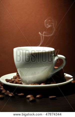 Cup of coffee with smoke on brown background