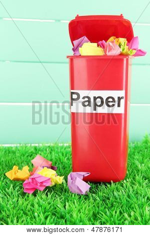 Recycling bin with papers on grass on light blue background