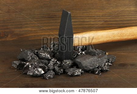 Coal with hummer on wooden background