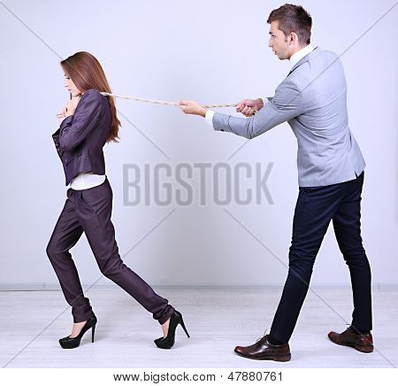 Business people stretching rope