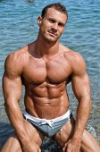 picture of kneeling  - Smiling attractive young bodybuilder shirtless in bathing suit kneeling on the beach - JPG