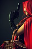 stock photo of cloak  - Cute Red Riding Hood with gun posing over dark background - JPG