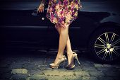elegant woman in high heel shoes getting into car