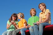image of happy kids  - group of happy kids playing with electronic games devices cell phones or listening to music - JPG