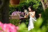 Woman Reading On Tablet In Garden