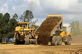 stock photo of dump  - A large track bulldozer and a large articulating dump truck at a new road project in Oregon - JPG