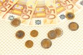 Euro banknotes and euro cents on beige background