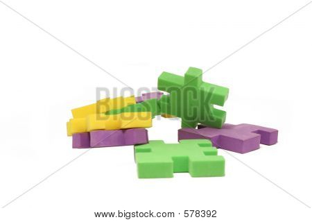 Picture or Photo of Several scattered green, purple & yellow foam jigsaw pieces isolated over white