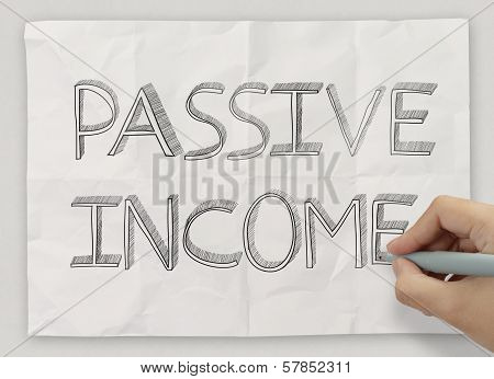 Close Up Of Hand Drawing Passive Income On Crumpled Paper Background As Concept