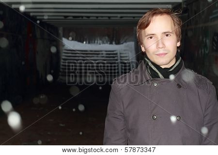 Man In Black Stands In Small Tunnel At Winter Night During Snowfall