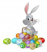 stock photo of white rabbit  - An Easter bunny white rabbit with a basket of painted chocolate Easter eggs - JPG