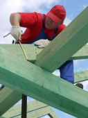 foto of purlin  - Carpenter taking measurement of house rafter beam - JPG