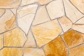 stock photo of porphyry  - Wall lined with light yellow porphyry stones - JPG