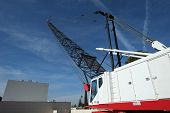 stock photo of boom-truck  - A crane with a one hundred foot mast has a long reach over this construction job site - JPG