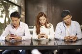 foto of addicted  - young people playing with smartphones and ignoring each other.