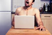 stock photo of orgasm  - Young Naked Man Watching Porn In His Kitchen - JPG