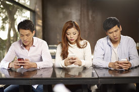 foto of inappropriate  - young people playing with smartphones and ignoring each other. ** Note: Shallow depth of field - JPG