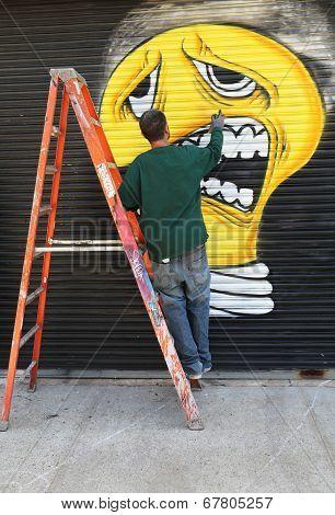 Street artist painting mural at Williamsburg in Brooklyn