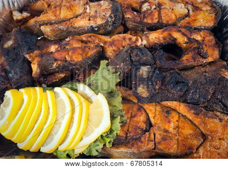 Grilled pink trout with lemon wedges and green.