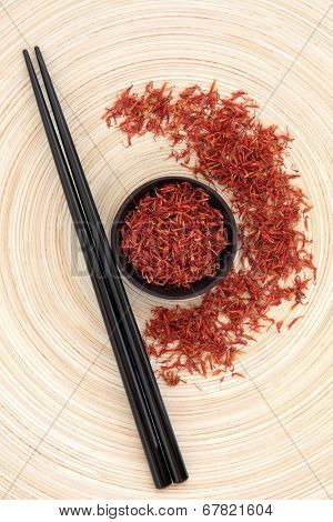 Safflower chinese herbal medicine with chopsticks on a circular wooden bowl. Hong hua.