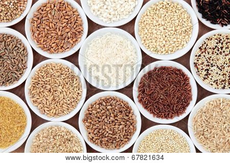 Grain and cereal food selection in white porcelain bowls over white background.