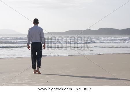 Businessman Walking Barefoot On A Beach