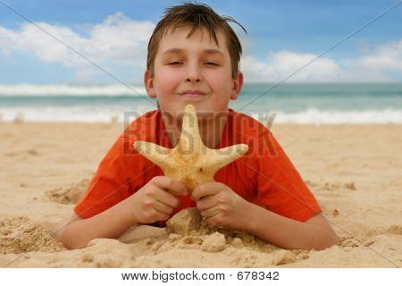 Boy On Beach Holding A Sea Star