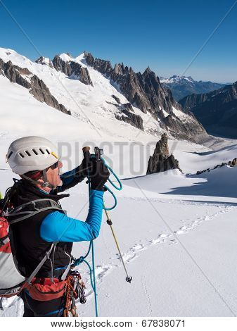 Mountaineer taking picture with a camera in the mountains. Mont Blanc Glacier, Chamonix, France, Europe.